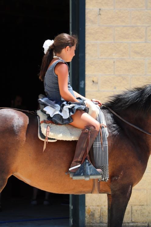 Young girl on horseback outside the pabellon