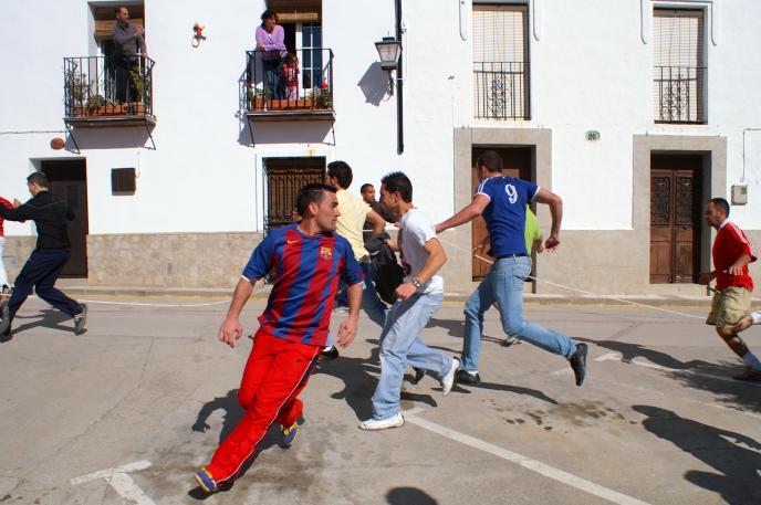 Villagers running from bull